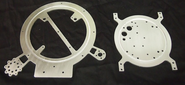 Lunokhod's Rim Plate and Base Plate. The two are held together by four long threaded machine screws. Each plate has a round slot so that when they are sandwiched together they hold the cone-shaped body in place. The base plate includes four extensions that hold the four rockers. It also has many holes for securing the electronics and other components. The rim plate includes holes for securing the conical antenna, directional antenna, eyes, and antennas.