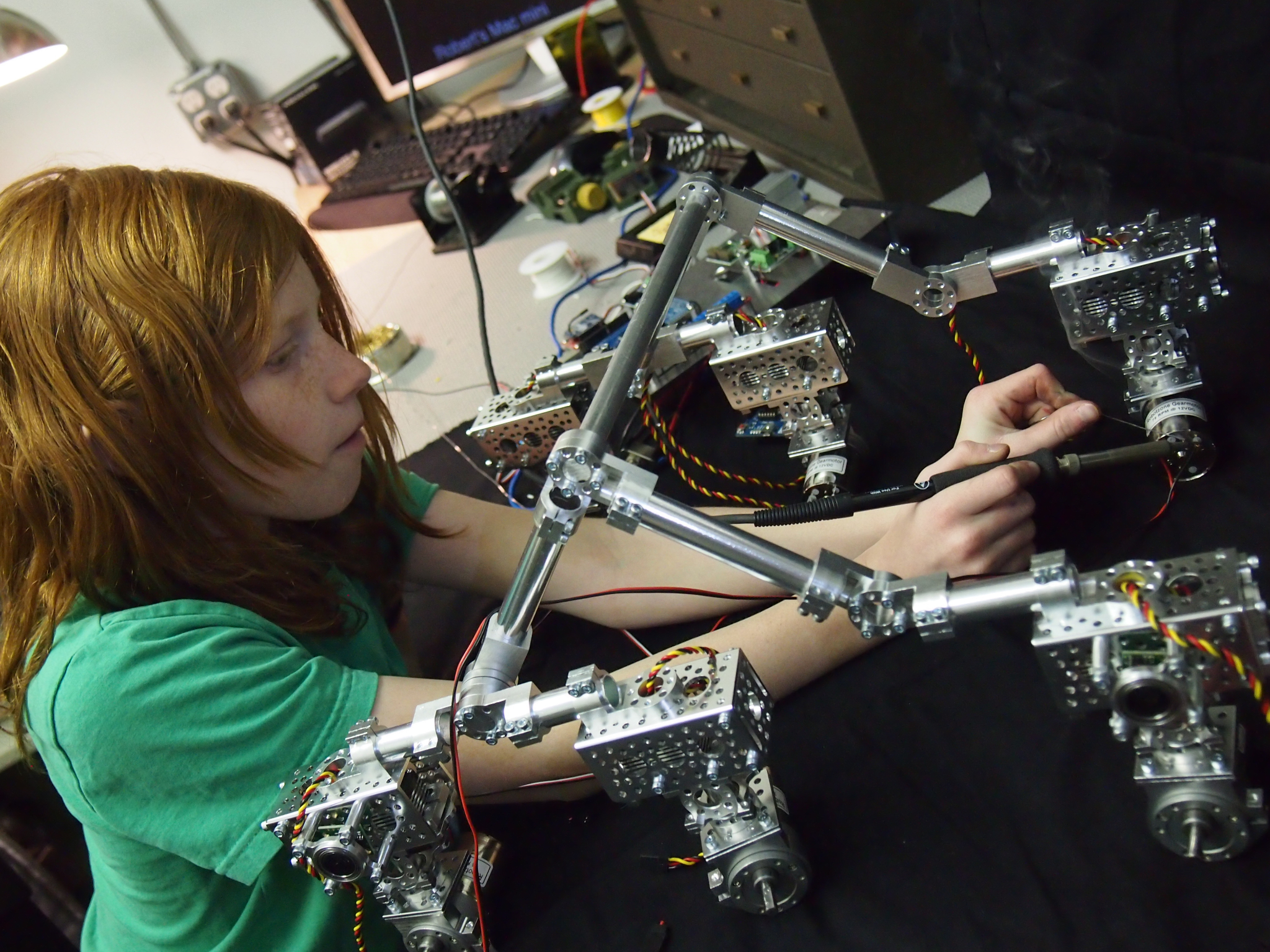 Genevieve soldering the wires onto the motors.