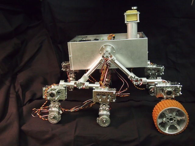 The Mars Rover is starting to take shape. The two sides of the rocker-bogie suspension system have now been installed on the main box. We put one of the wheels in place to show what it will look like. The motor, servo, and two sonar sensors are soldered on the front wheel, but not the back two (thus the hanging wires).