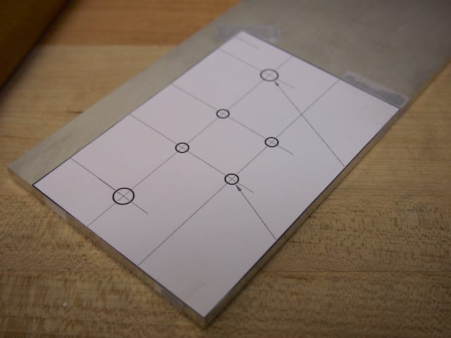 When we were building the CNC we often joked that it would have been convenient to have a CNC to build our CNC. It's hard to be precise without one. One of the techniques we used was to print out the pattern on our laser printer, tape it to the aluminum plate, then start manually cutting and drilling.