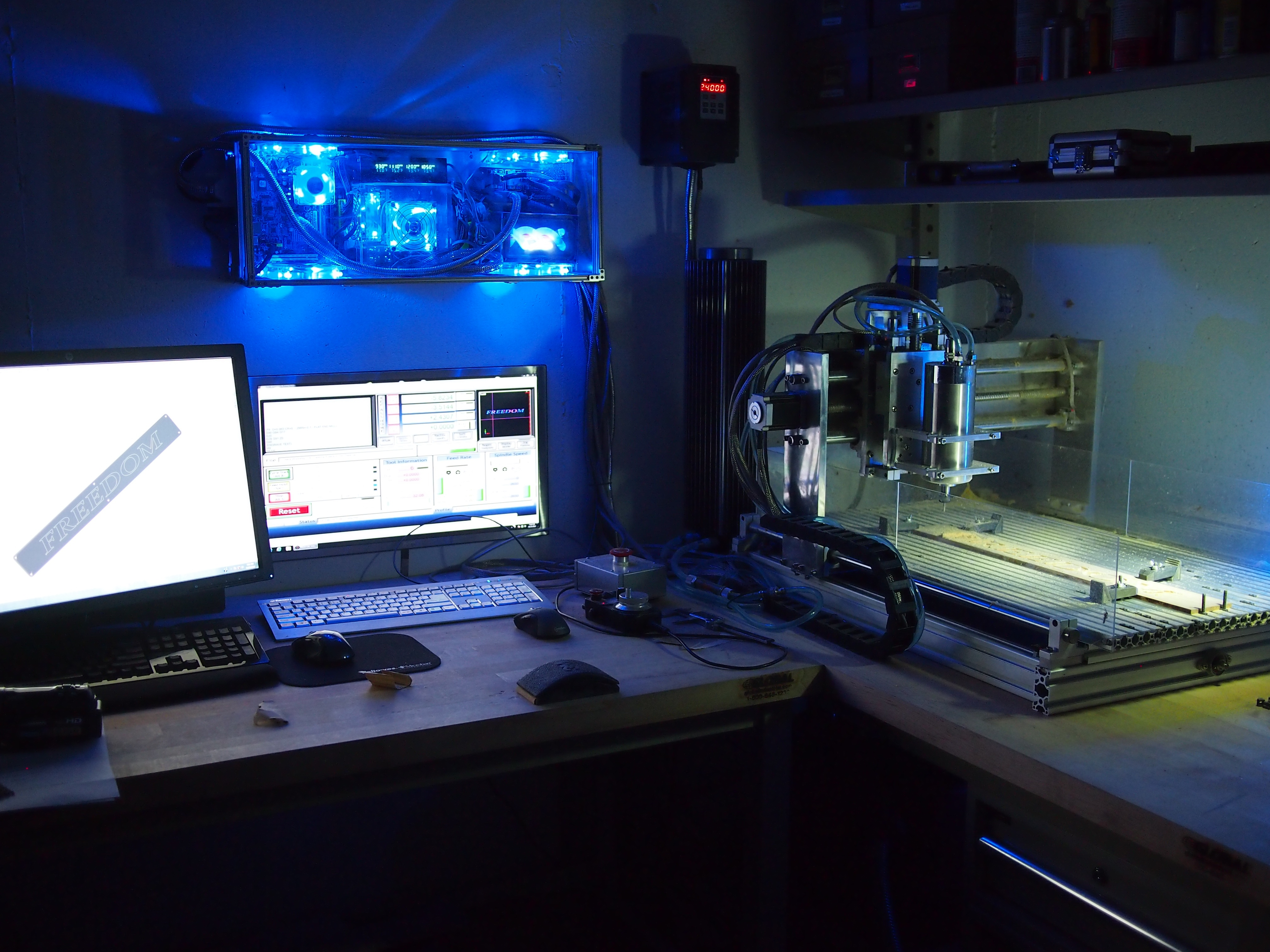 Machining a sign plate: From left to right: The CAD drawing displayed on SolidWorks CAD station, the CNC computer/controller (the blue glowing box), the CNC screen, the VFD spindle controller (with red digital read out), the cooling tower, and the CNC itself (on the right) with the part being machined.