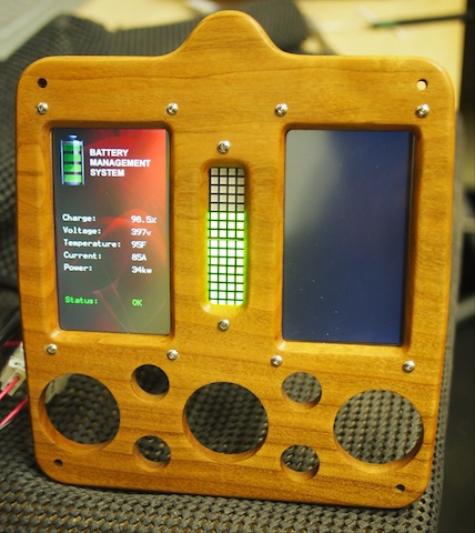 A custom dashboard console machined out of solid cherry on the CNC for an electric car.